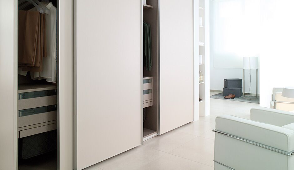 Sliding creamy white painted wooden door closet